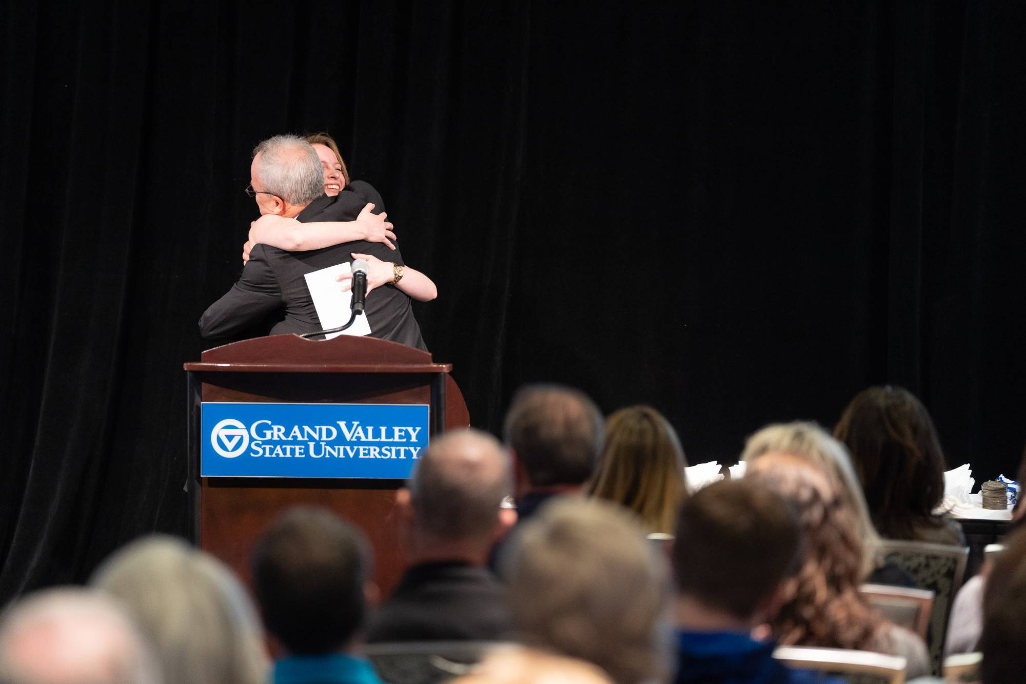 Professor Benjamin hugging Outstanding Senior Award winner Julia Clay.
